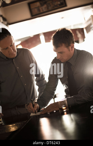 Two businessmen signing contract in wine bar - Stock Photo