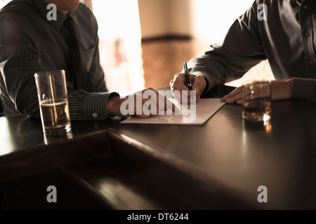 Partners signing business contract in a bar - Stock Photo