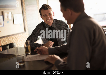 Business partners signing contract in a wine bar - Stock Photo