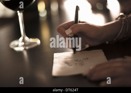 Close up of young woman writing her phone number on a napkin in bar - Stock Photo
