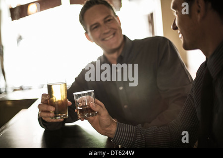 Two businessmen toasting drinks at the bar - Stock Photo