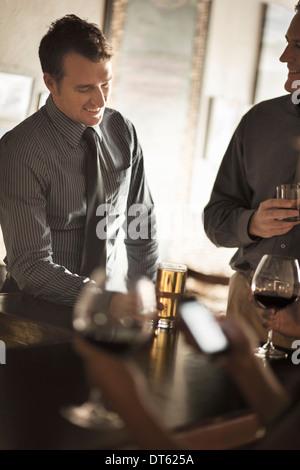 Business friends enjoying drinks in a wine bar - Stock Photo
