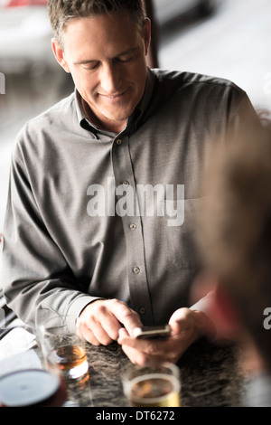Businessman using cellphone in a wine bar - Stock Photo