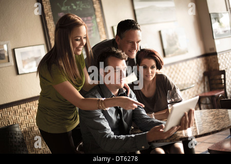 Friends looking at digital tablet in wine bar - Stock Photo