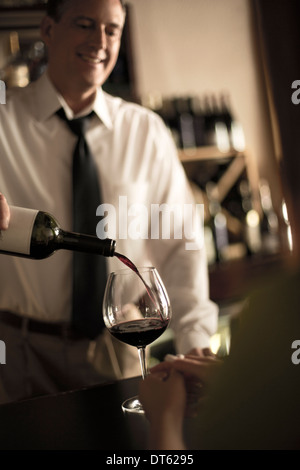 Bartender pouring red wine in bar - Stock Photo