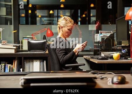 Female office worker at desk using cell phone - Stock Photo