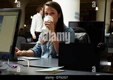 Young woman drinking coffee in office - Stock Photo