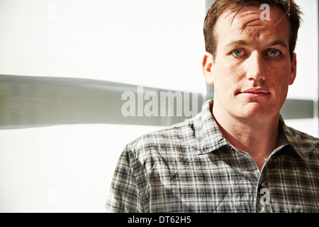 Portrait of mid adult man wearing checked shirt - Stock Photo
