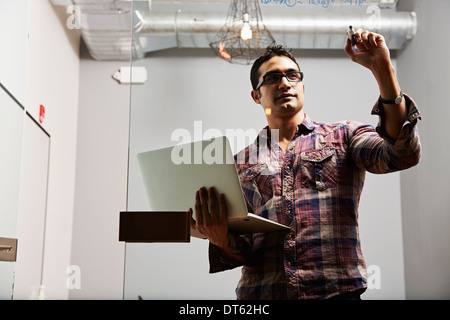 Young man holding laptop writing on glass - Stock Photo