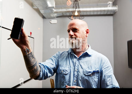 Mature man using whiteboard eraser - Stock Photo