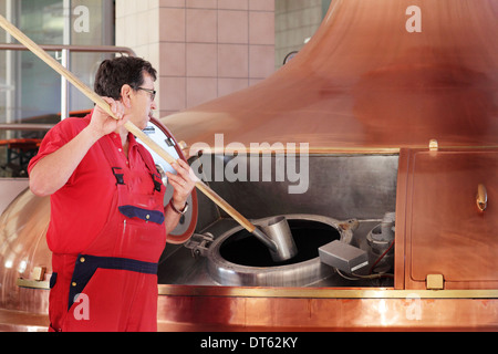 Man stirring vat in brewery