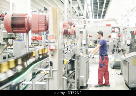Man working on production line in brewery - Stock Photo