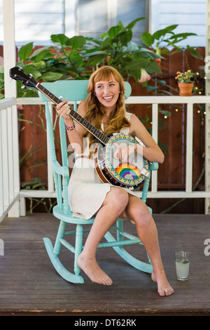 Young woman sitting on rocking chair playing banjo - Stock Photo