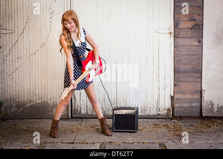 Young woman playing electric guitar outside garage - Stock Photo