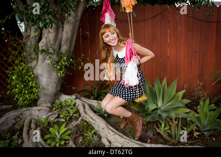 Young woman sitting on swing in garden - Stock Photo