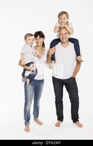 Studio portrait of parents with their young daughter and toddler son - Stock Photo