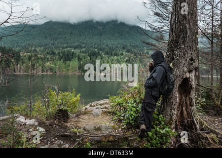 Man wearing waterproof clothes by tree, Buntzen Lake, British Columbia, Canada - Stock Photo