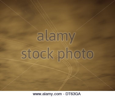 Light trails from aircraft taking off in overcast night sky - Stock Photo