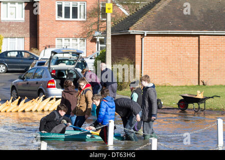 Datchet, UK. 10th Feb, 2014. Children with an inflatable dinghy in flooded Datchet village. Sandbags placed along - Stock Photo