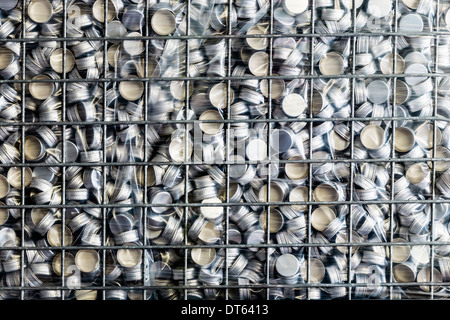 Wire cage full of bottle tops in bottling plant - Stock Photo