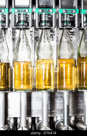 Close up of bottles on conveyor belt - Stock Photo
