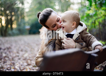 Mother holding male toddler on woodland park bench - Stock Photo