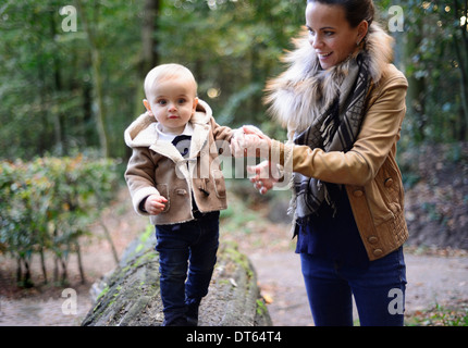 Mother walking male toddler on tree trunk - Stock Photo