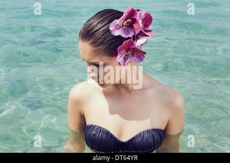Young woman wearing orchids in her hair wading in lake - Stock Photo