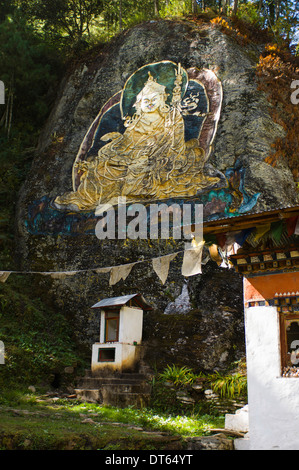 Bhutan, South Asia, Thimpu, Gold painted carving of Guru Rimpoche on rock wall. - Stock Photo