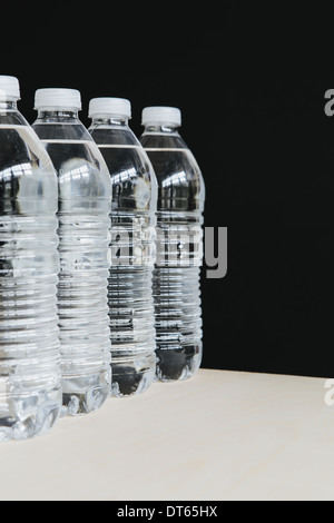 Row of clear, plastic water bottles filled with filtered water in a row. on a black background. - Stock Photo