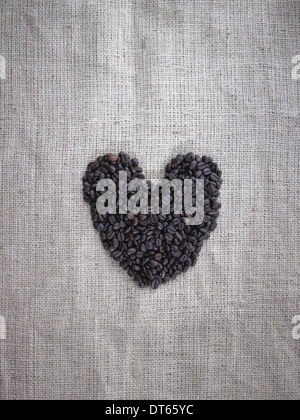 Organic roasted coffee beans in a heart shape on a burlap sack. - Stock Photo