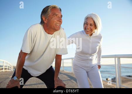 Couple doing squatting exercise - Stock Photo
