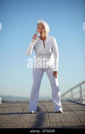 Mature woman drinking water on walk - Stock Photo
