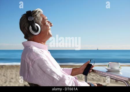 Senior man listening to music with headphones on beach - Stock Photo