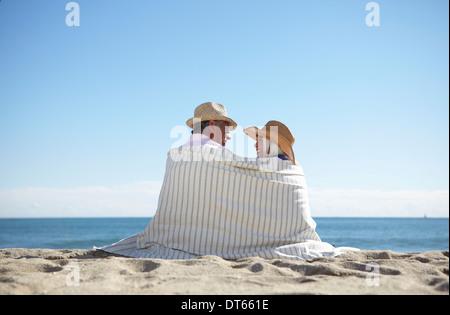 Couple wearing straw hats on beach - Stock Photo