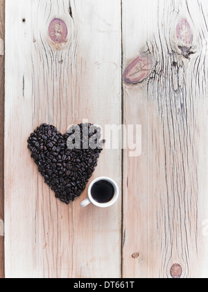 Overhead view of a heap of roasted organic coffee beans in a heart shape, arranged on a tabletop. A cup of black - Stock Photo
