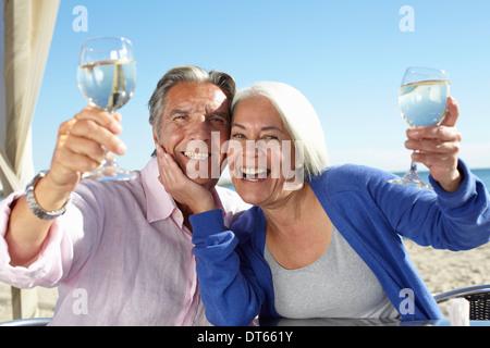 Couple enjoying wine by seaside - Stock Photo