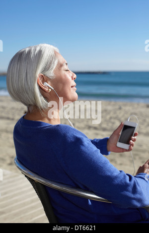 Mature woman listening to music with earbuds on beach - Stock Photo