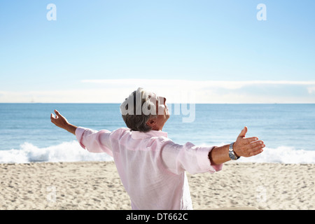 Senior man on beach with arms outspread - Stock Photo