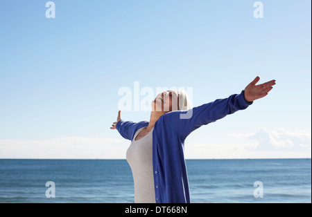 Mature woman on beach with arms outspread - Stock Photo