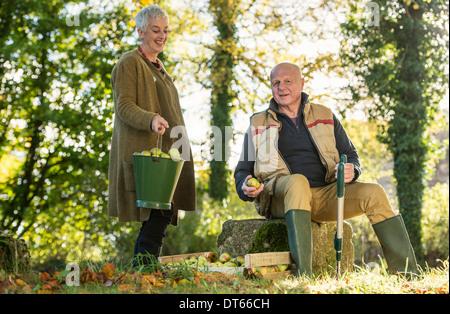 Senior couple taking a break in orchard - Stock Photo
