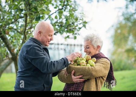 Portrait of happy senior couple with apples - Stock Photo
