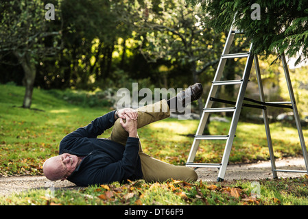 Senior man grimacing over injured knee - Stock Photo