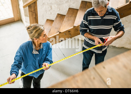 Senior couple doing DIY, using measuring tape - Stock Photo