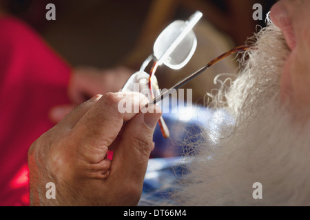Senior man chewing end of spectacles - Stock Photo