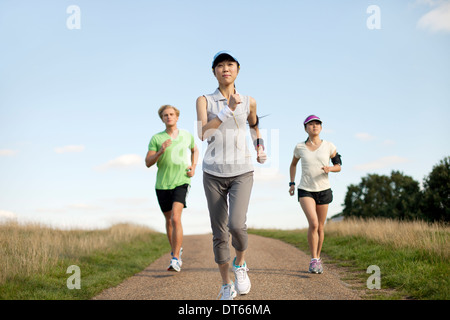 Three young adults jogging along field track - Stock Photo