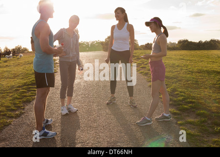 Personal trainer with group of clients preparing for run - Stock Photo