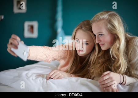 Two teenage girls taking selfie in bedroom - Stock Photo