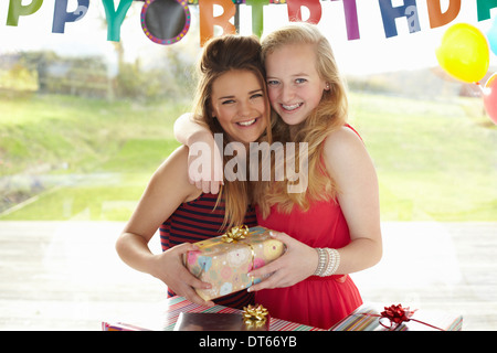 Teenage girl and friend with birthday gift - Stock Photo