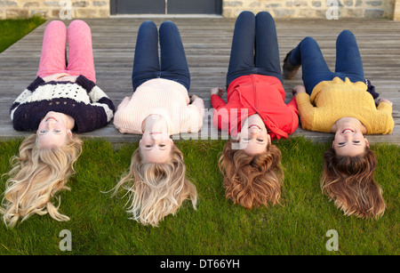 Four teenage girls lying on patio and looking back - Stock Photo